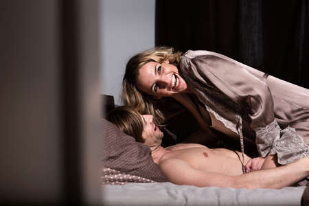 Couple in bed,woman laughing
