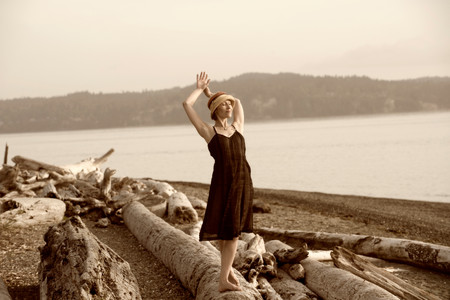 Woman standing on driftwood and stretching