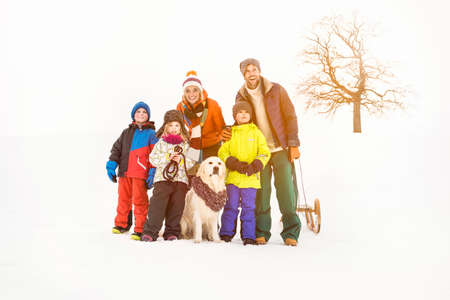 sledging people: Family with three children standing in snow LANG_EVOIMAGES