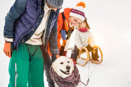 Man and woman with dog,daughter in background on toboggan