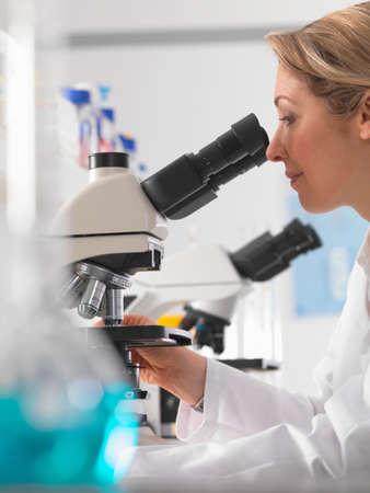 specimen testing: Female microbiologist viewing specimen under microscope in lab