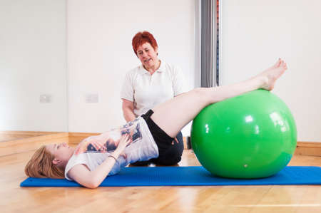 recuperating: Young woman exercising with fitness ball,guided by mature woman