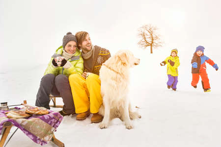Parents with dog and children playing in background LANG_EVOIMAGES
