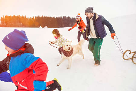 30 years old man: Family running in snow with dog