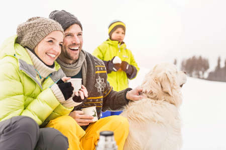 pooches: Man and woman with hot drinks and dog,son in background LANG_EVOIMAGES
