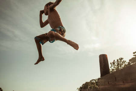 low self esteem: Boy jumping off jetty