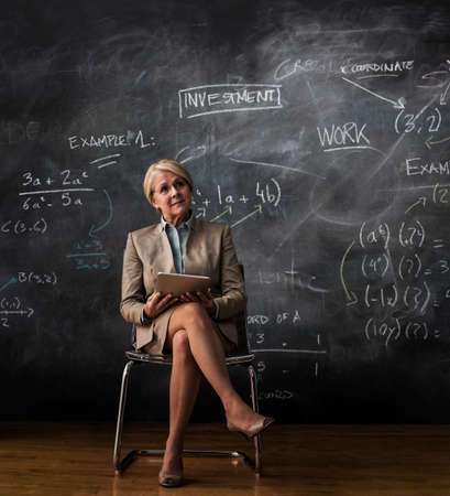 numeric: Businesswoman sitting on chair with digital tablet and blackboard