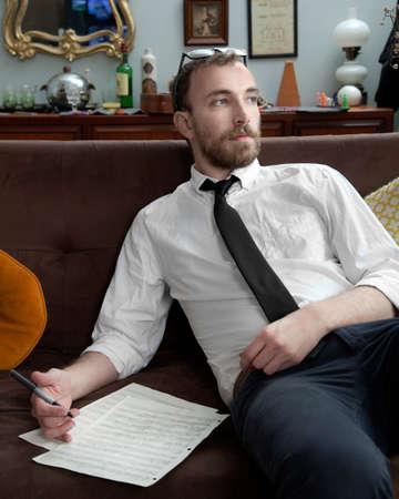 musical score: Young man writing sheet music and looking away