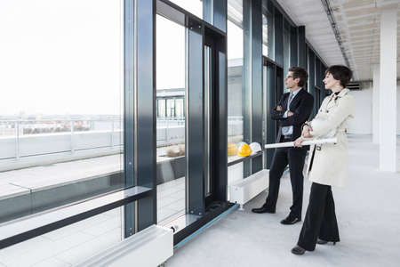 businessman pondering documents: Architects looking out of window with blueprint