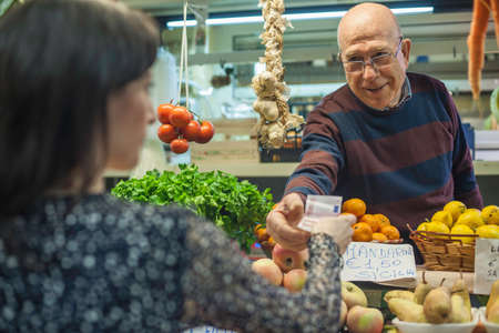 shop keeper: Shopkeeper handing change to female customer in market