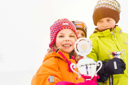 Portrait of children holding trophies LANG_EVOIMAGES