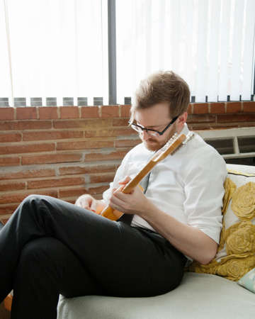 couch: Young man practising on electric guitar