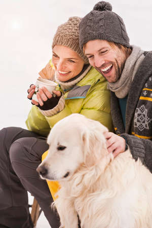 Mid adult couple wearing knit hats with dog