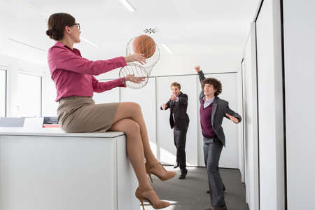 Office workers playing basketball with litter bin