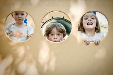 playground rides: Three children making faces through circles LANG_EVOIMAGES