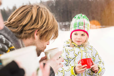 Father and daughter drinking hot drinks outdoors