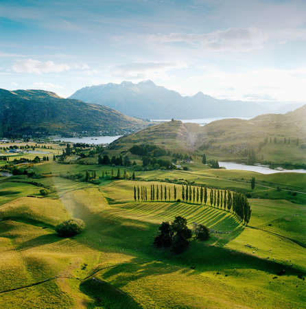 farmyards: View across farmland towards lakes and Southern Alps from helicopter,Queenstown,Southern Alps,South Island,New Zealand