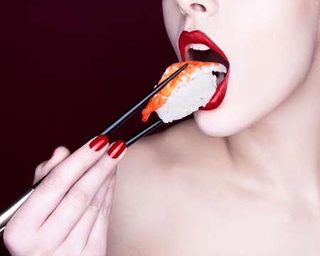 Woman eating sushi LANG_EVOIMAGES