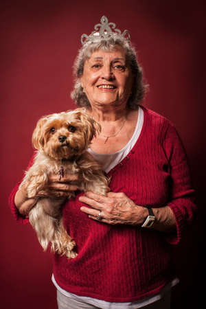 pooches: Senior woman holding dog and wearing a tiara