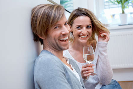 Couple in kitchen with wine