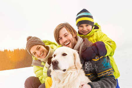 Parents and son with dog in snow LANG_EVOIMAGES