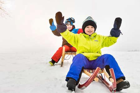 Two boys on toboggans in snow LANG_EVOIMAGES