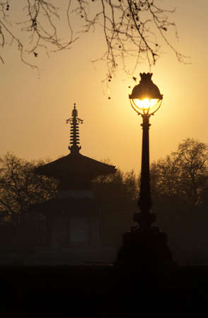 An old bandstand and street light silhouetted again a low sun in London,UK LANG_EVOIMAGES