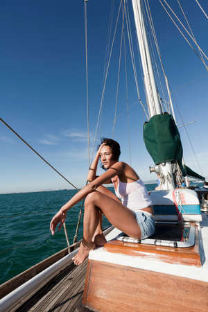 Young woman on deck of yacht LANG_EVOIMAGES