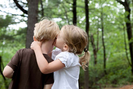 Girl whispering to boy friend in the woods LANG_EVOIMAGES