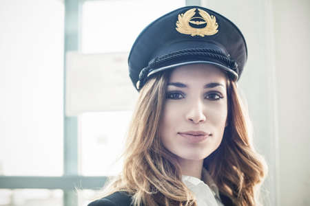 authoritative woman: Female pilot wearing hat LANG_EVOIMAGES