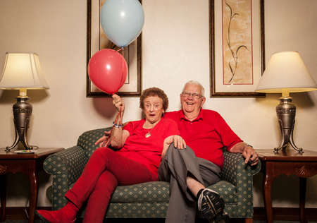 Senior couple on sofa with balloons LANG_EVOIMAGES