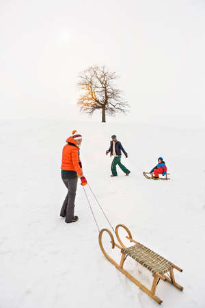 Woman pulling toboggan in snow LANG_EVOIMAGES