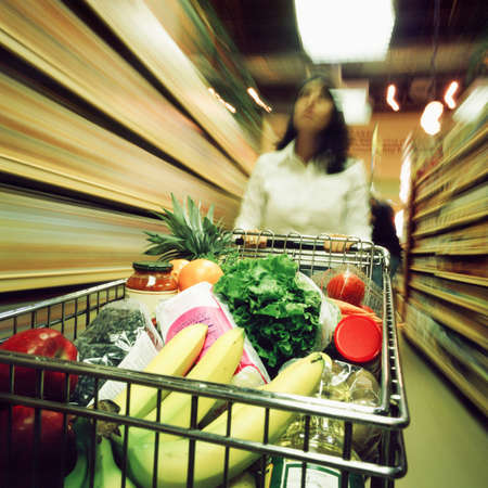 supermarket: Woman in supermarket with trolley,motion blur
