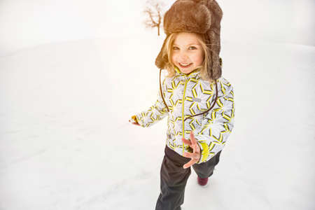 Dívka na sobě chlupatý klobouk ve sněhu