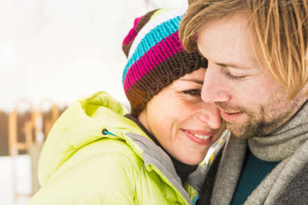 Mid adult couple embracing,woman wearing knit hat LANG_EVOIMAGES