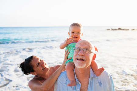 Grandparents with granddaughter on grandfathers shoulders,St Maarten,Netherlands