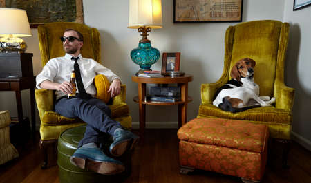 beer necktie: Young man and pet dog relaxing in armchair in living room LANG_EVOIMAGES