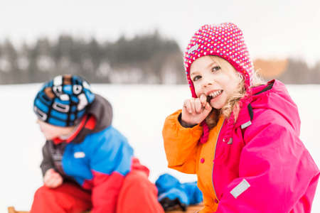 Girl and boy wearing winter clothes,girl looking at camera LANG_EVOIMAGES