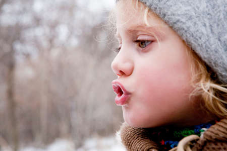 puckered: Little girl looking at her breath in the cold air