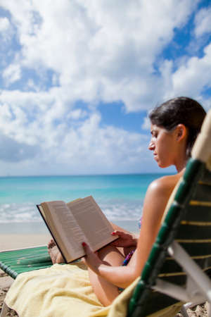 Woman reading book on beach,St Maarten,Netherlands