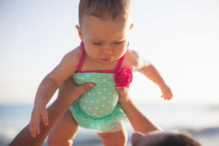 protective suit: Woman lifting baby girl wearing swimsuit LANG_EVOIMAGES