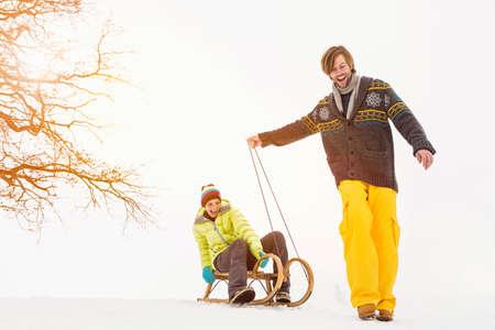 Man pulling woman through snow on toboggan LANG_EVOIMAGES