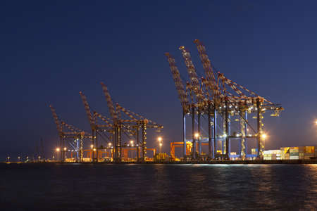 Cranes in shipyard lit up at night