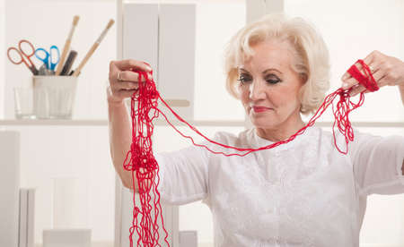 Senior woman with tangled wool