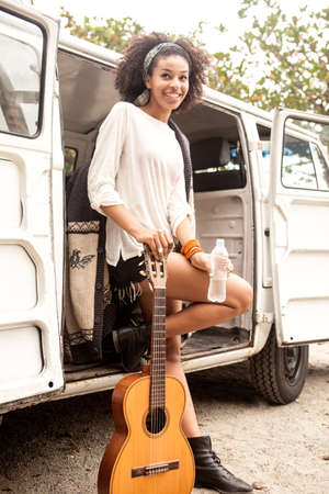 Young woman with guitar leaning on camper van,Rio De Janiero LANG_EVOIMAGES