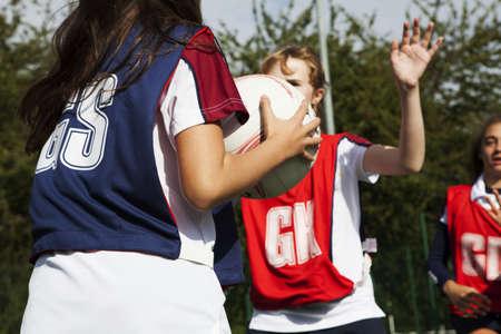 Teenage schoolgirl netball players defending LANG_EVOIMAGES
