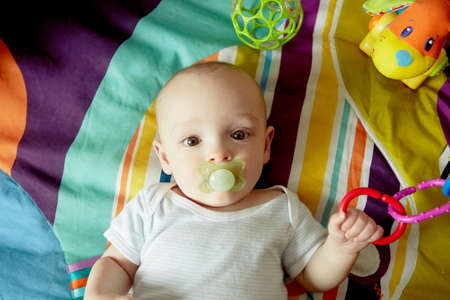 babys dummies: Baby boy lying on blanket sucking pacifier and playing with toys