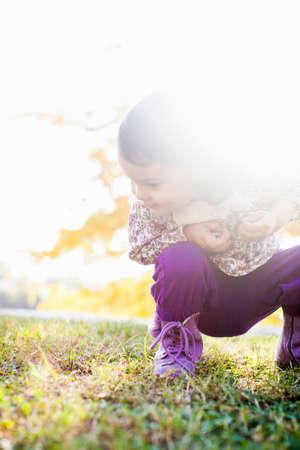 pantalones abajo: Niño en cuclillas mirando hacia abajo a la hierba
