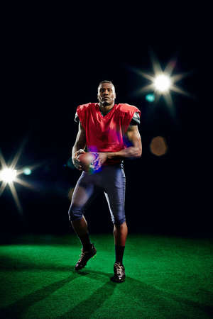 strips away: American football player holding ball LANG_EVOIMAGES