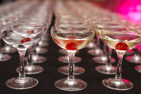 Rows of drinking glasses with maraschino cherry inside
